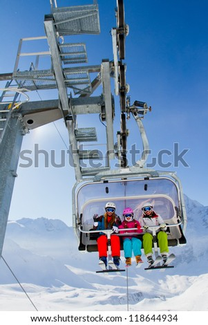 Ski lift, skiing, ski resort  - happy skiers on ski lift - stock photo