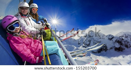 Ski lift, skiing, ski resort - happy skiers on ski lift