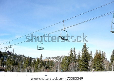 Ski Lift with Blue Sky, Forest, and Snowy Slope - stock photo