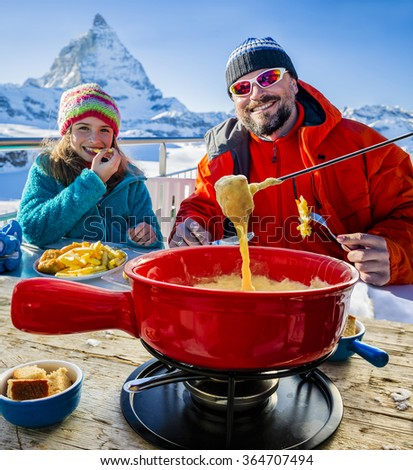 Ski lunch in a restaurant, Fondue, traditional Swiss dish - Matterhorn in Swiss Alps in background - stock photo