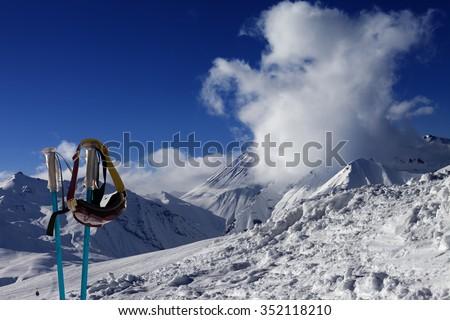 Ski mask on ski poles and off-piste slope in sun cold day - stock photo