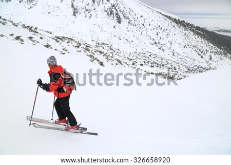 Ski mountaineer ascending a white slope on skins during snowy weather - stock photo
