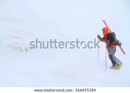 Ski mountaineer ascending snowy slope in bad weather - stock photo