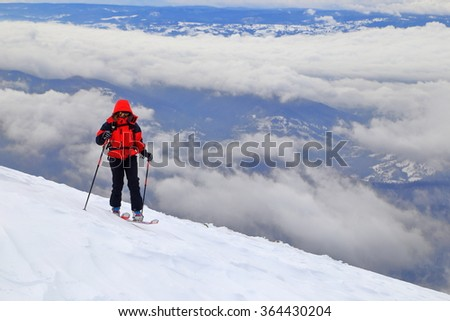 Ski mountaineer climbing on steep mountain above the clouds - stock photo