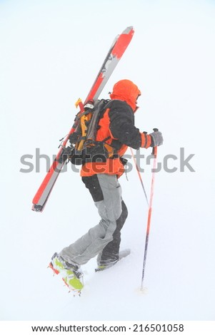 Ski mountaineer climbs steep slope in adverse weather - stock photo