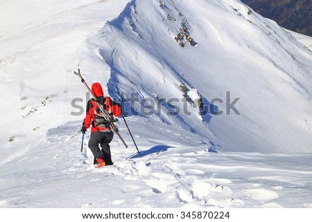 Ski mountaineer descending a snowy ridge with skis on the backpack