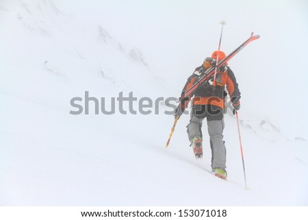 Ski mountaineer on the snowy slope in bad weather - stock photo