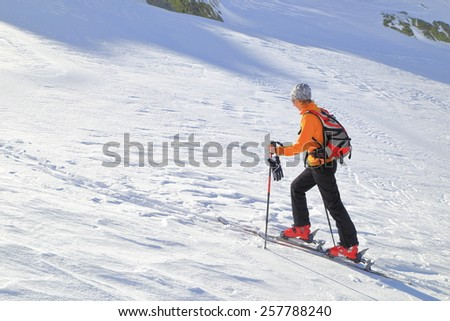 Ski mountaineer skinning up a steep sunny slope - stock photo