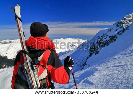 Ski mountaineer standing on the mountain with skis on the backpack - stock photo