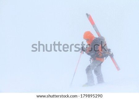 Ski mountaineer surrounded by fog and snow fall  - stock photo