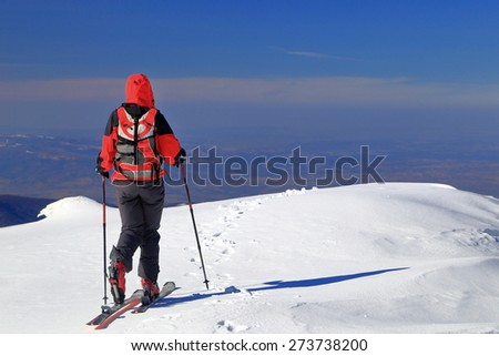 Ski mountaineer traversing a white snow field in sunny winter day - stock photo