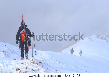 Ski mountaineer walking a snowy mountain ridge with skies attached to the backpack - stock photo