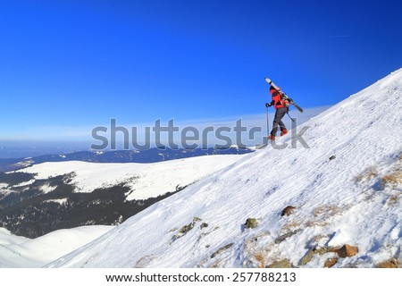 Ski mountaineer woman descending a steep slope with skies on the backpack