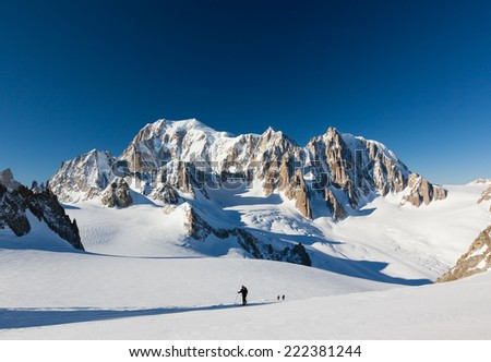 Ski mountaineers ascend the Vallee Blanche glacier. In background the est face of Mont Blanc. Chamonix, France, Europe. - stock photo