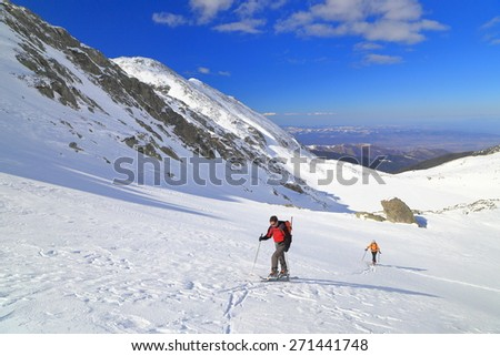 Ski mountaineers ascending large valley in sunny winter day - stock photo