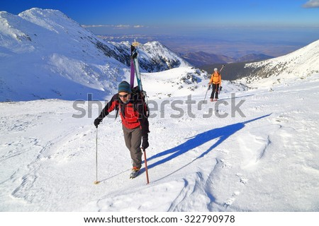 Ski mountaineers climb a frozen mountain with skis on the backpack - stock photo