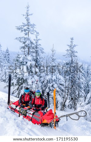 Ski patrol with rescue sled helping injured woman snow forest - stock photo