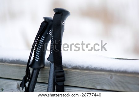Ski poles against a snow covered wooden rail. - stock photo