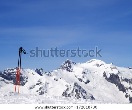 Ski poles and snowy mountains at nice day. Caucasus Mountains, Dombay.