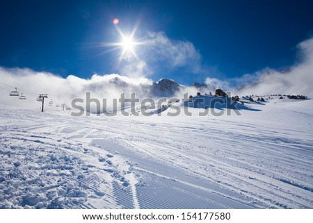 Ski resort piste slope and morning mist and low clouds on sunny day - stock photo