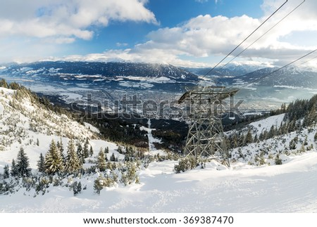 Ski run with snow-covered trees, city of Innsbruck and mountains in the background, photographed from Seegrube skiing region, Innsbruck, Tyrol, Austria - stock photo