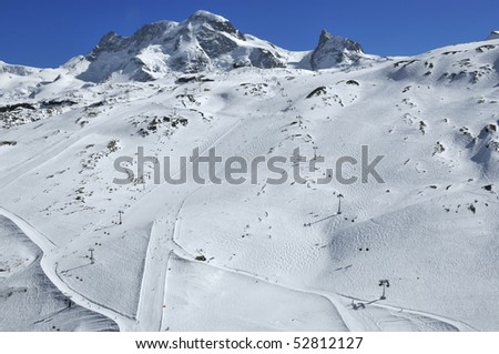 ski runs in the swiss ski resort of Zermatt with the peak of the breithorn and the kleine matterhorn (right) in the background - stock photo