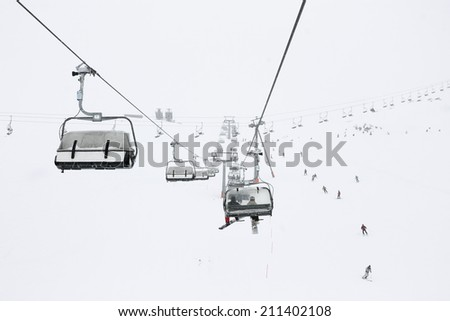 Ski season in the Alps. Panorama of the ski lifts during snowfall and fog. Picture taken in Austrian Alps - stock photo