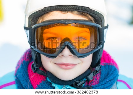 Ski, skier girl, winter vacation, snow, sun and fun - portrait of girl in goggles enjoying ski holiday - stock photo
