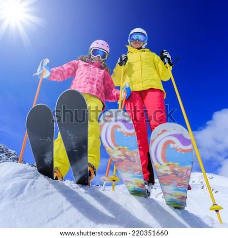Ski, skiers, sun and winter fun - skiers enjoying ski vacation - stock photo