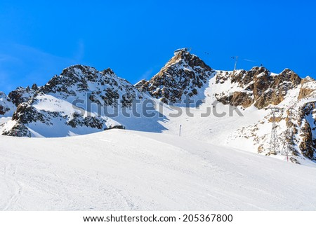 Ski slope and gondola cars on a lift in Austrian ski resort of Pitztal, Austrian Alps - stock photo
