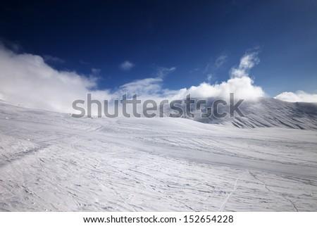Ski slope and mountains in clouds. Georgia, ski resort Gudauri. Caucasus Mountains. - stock photo