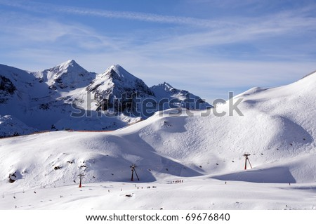 Ski slope with people skiing and snowboarding in touristic resort Obertauern in Austrian Alps mountain range in Austria - stock photo