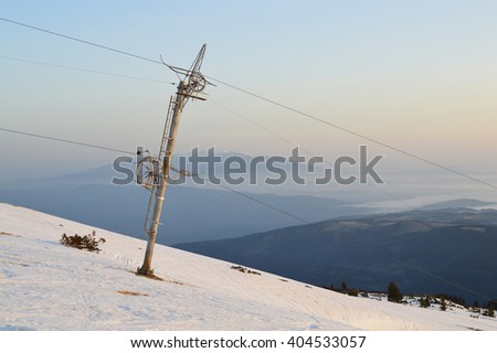 Ski slope with tow at sunrise, end of the ski season in Rila Mountains, Bulgaria. The silhouette of Vitosha Mountain seen on the horizon