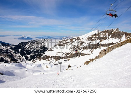 Ski slopes in the french alps. Downhill view above the clouds. A chair lift is taking skiers higher up out of the picture to the upper right. - stock photo