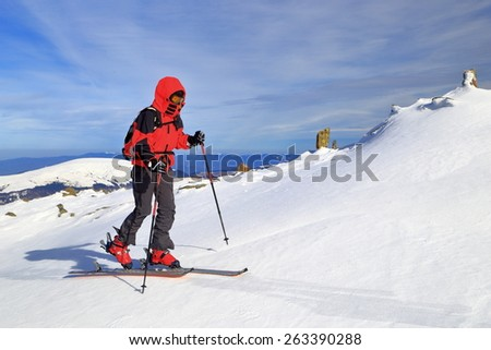 Ski tourer woman ascending white mountain slope in windy morning  - stock photo