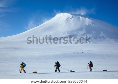 Ski touring group in colorful cloths with backpacks and sleds/pulkas on the background of a snowy mountain. Wind lifts snow from peak. Cross country skiing in northern Sweden beyond the Arctic Circle
