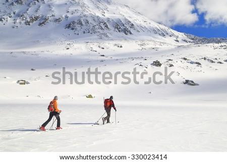 Ski touring trip on sunny mountain during winter - stock photo
