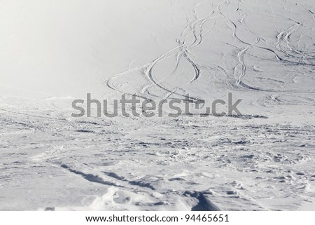 Ski traces on snow in winter mountains - stock photo