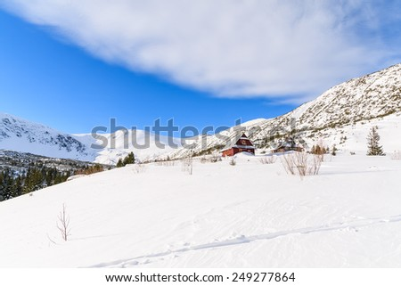 Ski track in fresh snow and wooden mountain huts in background in winter landscape of Gasienicowa valley, Tatra Mountains, Poland - stock photo