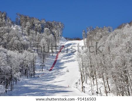 Ski track on a mounting skiing resort. Krasnaya Polyana, Sochi, Russia - stock photo