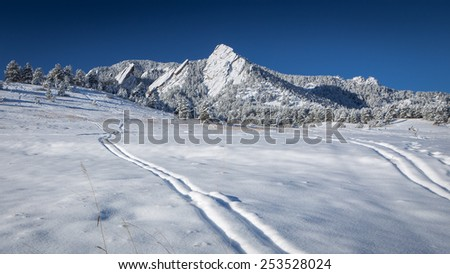 Ski Tracks in the Snow Below the Flatirons in Boulder, Colorado's Chautauqua Park  - stock photo