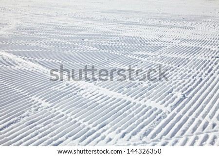 Ski tracks on a fresh groomed piste - stock photo
