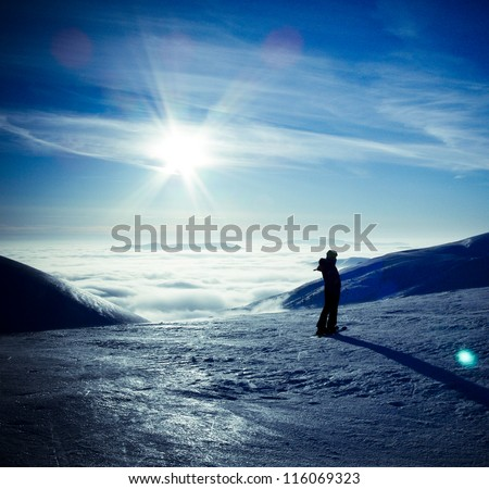 Ski traveler woman silhouette in amazing winter mountains landscape, over the clouds, opposite to sunset sky