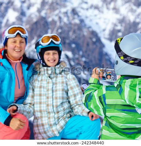Ski, winter, snow, skiers, sun and fun - boy photographed family on phone during winter vacations. - stock photo