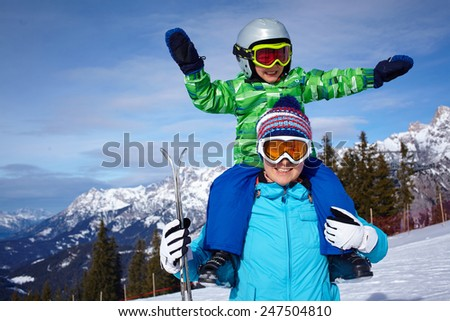 Ski, winter, snow, skiers, sun and fun - Family - mother and son enjoying winter vacations - stock photo
