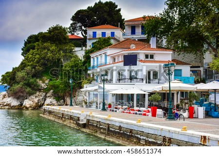 Skiathos town greek tavern by the sea with fishing boat and blue water, Greek island - stock photo