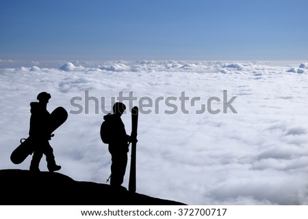 Skier and snowboarder silhouette high above the clouds in mountains. Snowboarder walking to the standing skier during a sunset, colorful sky in front of them. Couple of freeriders on the hill.