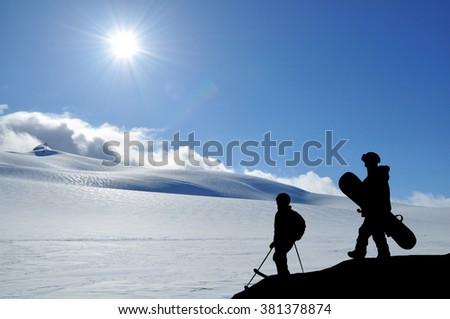 Skier and snowboarder silhouette high in mountains. Snowboarder walking to the standing skier, snowy hills and sun in front of them. Couple of freeriders on the hill. - stock photo