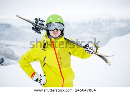 Skier carrying skis - stock photo