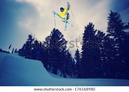 Skier Catching Big Air off jump at sunset - stock photo